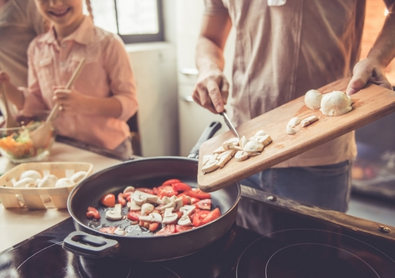 family cooking meal together in kitchen