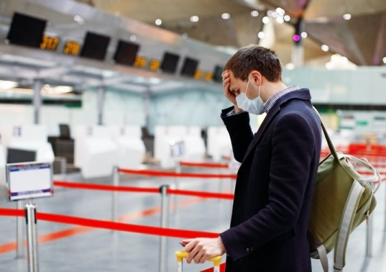 Man looking worried and wearing a mask at the airport