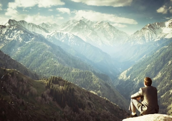Person sitting look at the view of mountains