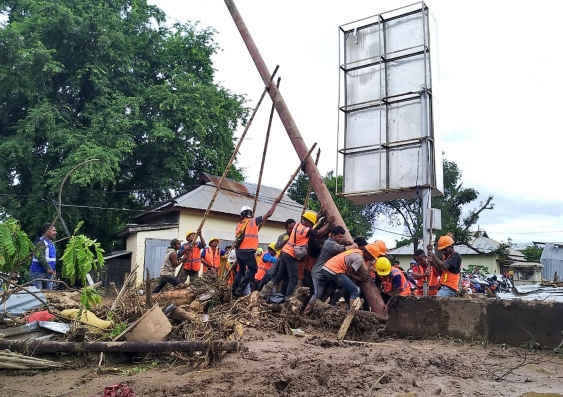 Indonesian workers replacing electricity poles in a flood zone