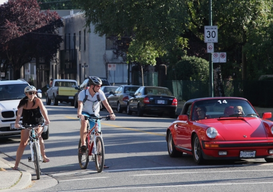 people on bicycles and a red car