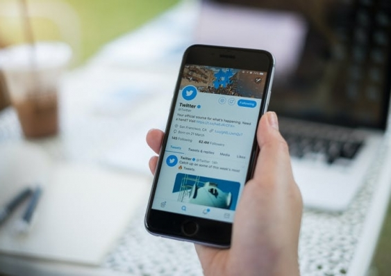 A person holds a mobile phone with Twitter app open
