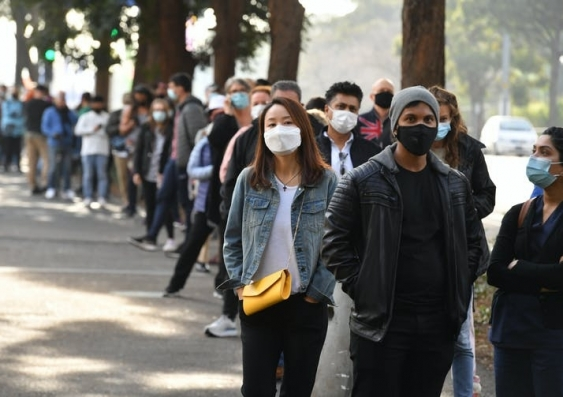 People wearing masks wait in line for a COVID-19 test