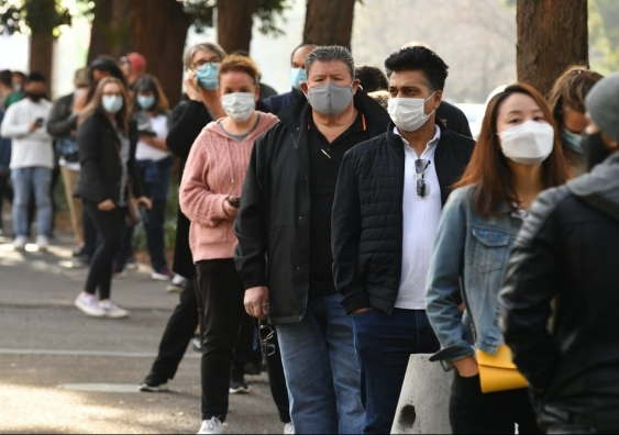 People waiting in line with masks on