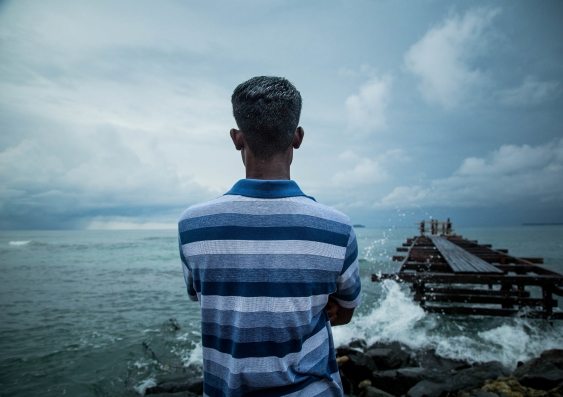 man looking out onto the water
