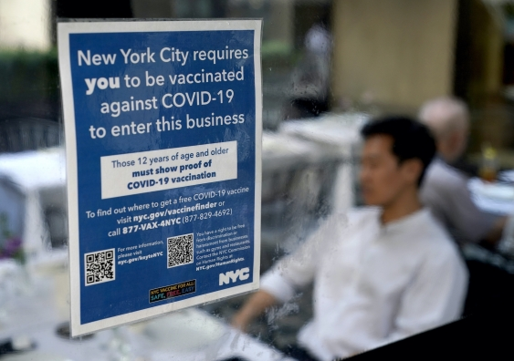 sign on restaurant window stipulating people have to show proof of vaccination