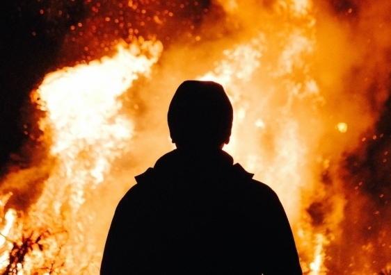 Man stands in front of fire
