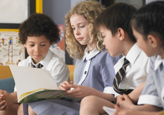 Four primary school students in uniforms reading a book together