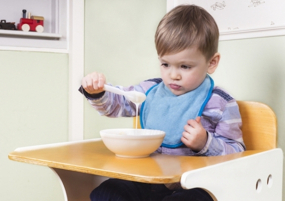 A child in a high chair plays with a bowl of food