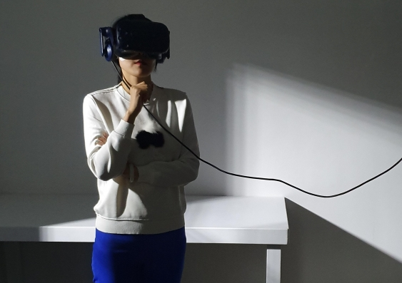 Woman using VR goggles to experience The Edge of the Present VR experience photo - Jessica Maurer