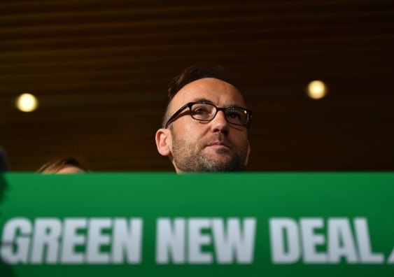 greens leader adam bandt at a lectern saying 'green new deal'