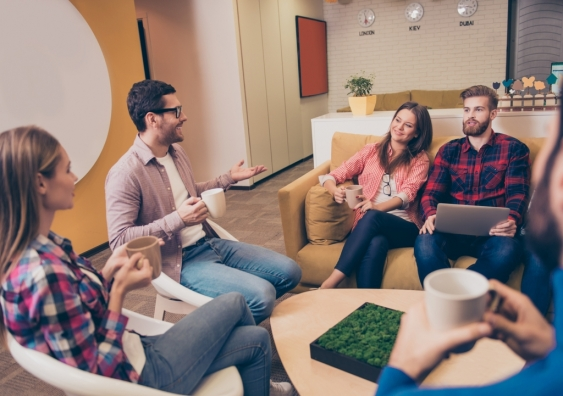 Group of casually dressed employees discuss ideas in the office