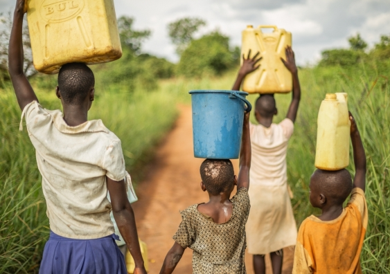 A group of young African children carry buckets of water on their heads.