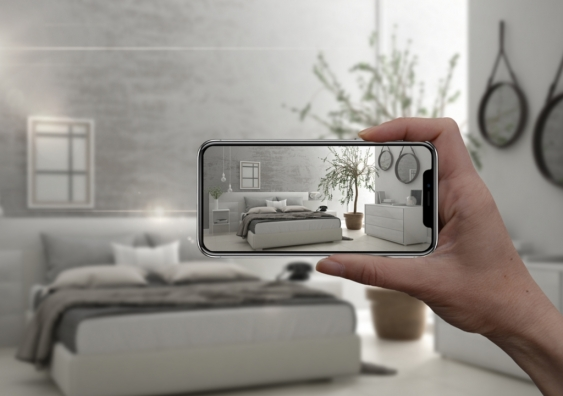 Hand holding smart phone with AR application simulating a bedroom