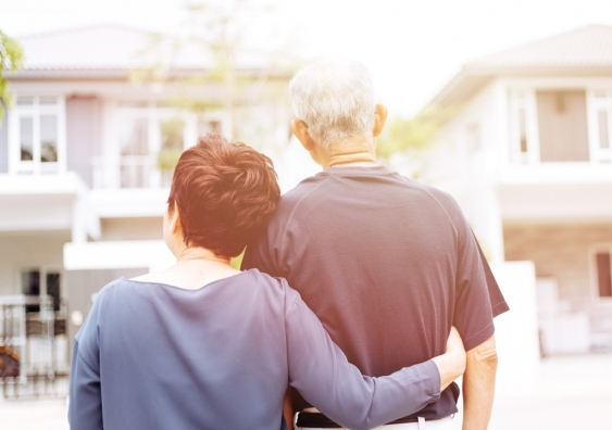 Older couple from behind looking at front of house