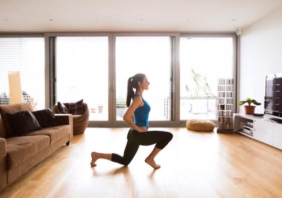 A woman does a lunge exercise in her living room