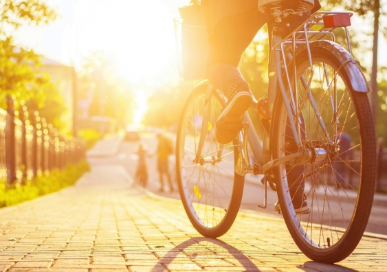 Close-up of an employee cycling down the street to a work hub