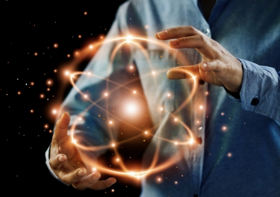 illustration of a scientists hands holding golden atoms in motion