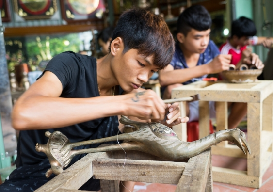 junior craftsmen making copper handicraft products in traditional method