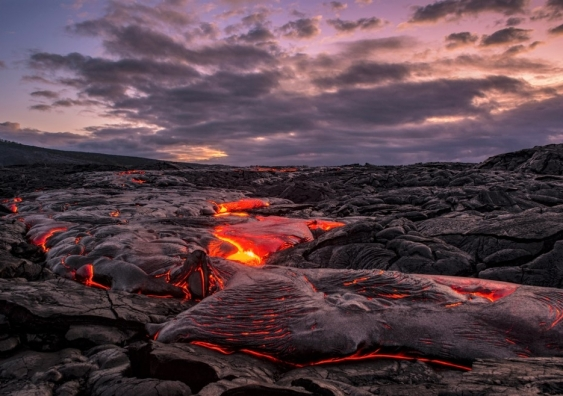 Lava flowing over rocks under a cloudy dawn sky