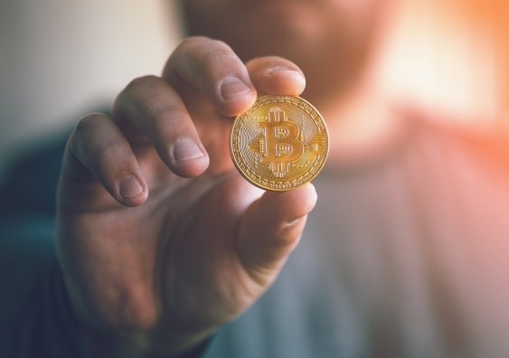 Man holds out gold symbol of Bitcoin