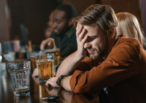 man holding his head in pain while drinking at a public bar