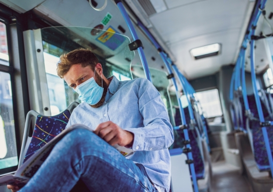 Man wearing face mask reading newspaper on a bus