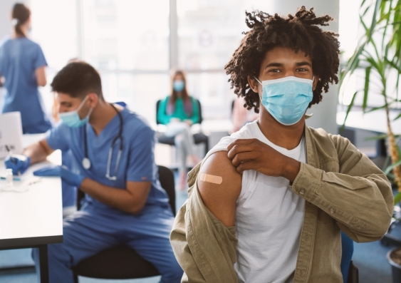 Man wearing face mask showing bandaid on arm where he just received COVID vaccination