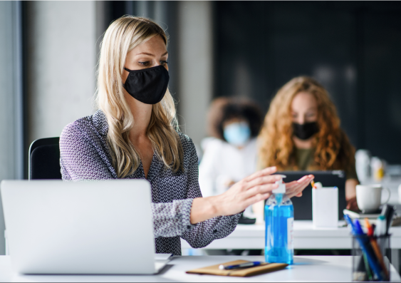Woman sitting at desk in workplace with mask on using hand sanitizer.