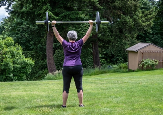 Older woman weight training in a park
