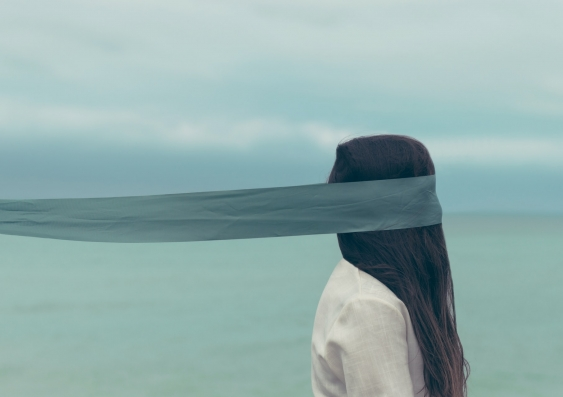 Blindfolded woman with long hair by the seaside