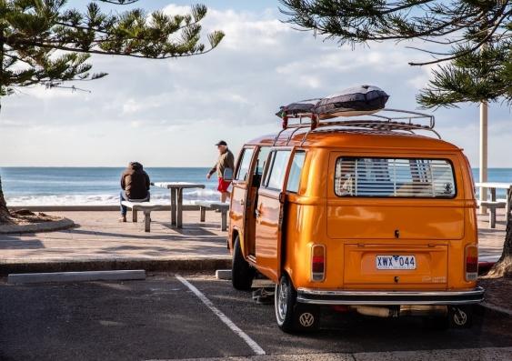 parked orange van overlooking beach