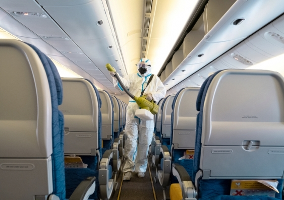 Person in PPE suit deep cleans the interior of an aeroplane