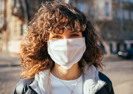 Portrait of a young woman wearing a white protective face mask