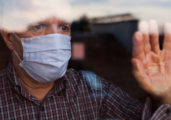 Senior man wearing face mask looking out window