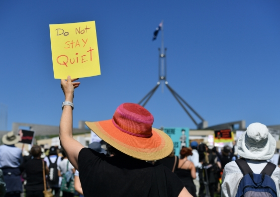 protester holds a sign at federal parliament saying do not stay quiet