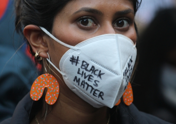"""Young female protester wearing a mask that reads """"Black Lives Matter"""""""