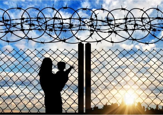 A mother holding a child next to a fence.