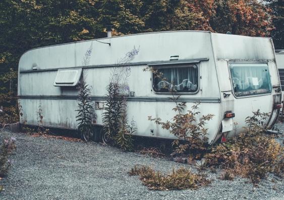 run down caravan with weeds