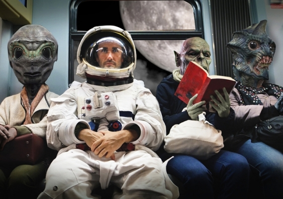 Astronaut and aliens seated in a space bus