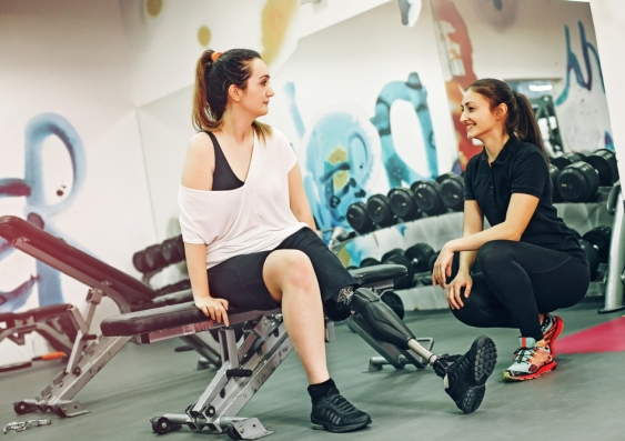 Woman in gym with prosthetic leg and personal trainer