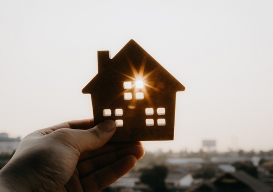 A person holding a house model against the sky.