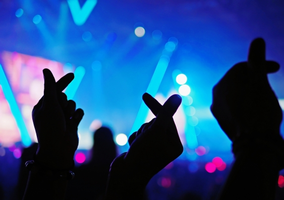 K-Pop music live concert background with silhouette hands of audience making mini heart shaped hand gestures