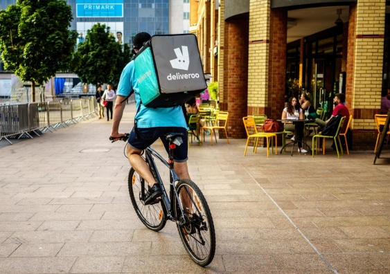 A Deliveroo delivery person riding a bike.