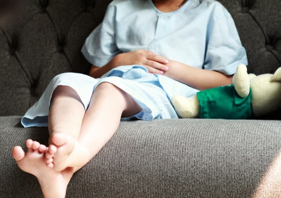 legs of patient kid in blue patient suit sitting on sofa and touch or press on her abdomen with her doll.