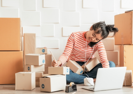 A woman sitting on the floor surrounded by boxes and taking orders on the phone.