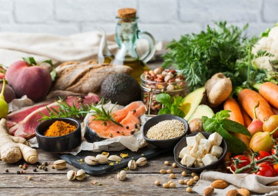 Assortment of healthy food ingredients for cooking on a wooden kitchen table.