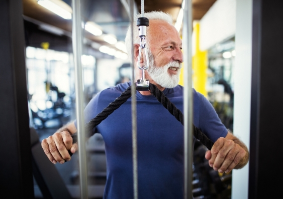 Smiling older man using weight machine at the gym