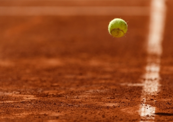 A tennis ball bounces on a clay court