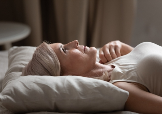 Sleepless mature woman with open eyes lying on soft pillow close up